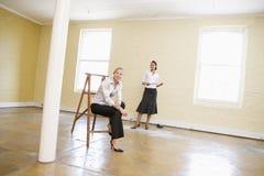 Mulheres de negócios que olham o espaço de escritórios novo Fotografia de Stock Royalty Free