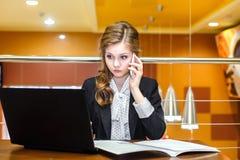 Mulheres de negócios que sentam-se em um café com um portátil e uma fala Fotografia de Stock Royalty Free