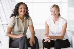 Mulheres de negócios que sentam-se na entrada imagem de stock royalty free
