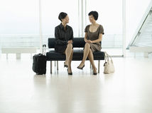 Mulheres de negócios que sentam-se na entrada do aeroporto Fotografia de Stock Royalty Free