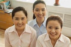 Mulheres de negócios que sorriem e que olham acima na câmera, no escritório Foto de Stock