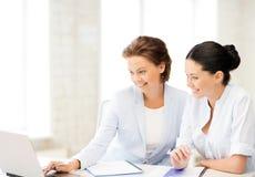 Mulheres de negócios que trabalham com o portátil no escritório Imagem de Stock