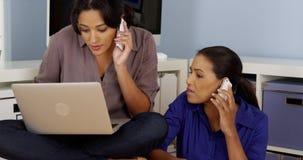 Mulheres de negócios que trabalham junto ao falar em telefones celulares Imagem de Stock Royalty Free
