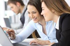 Mulheres de negócios que trabalham junto com um portátil Fotos de Stock