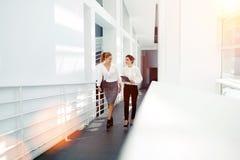 Mulheres de negócios satisfeitas com tabuleta digital e originais que voltam após ter encontrado empregadores, Fotos de Stock Royalty Free