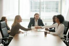 Mulheres de negócios de sorriso diversas que agitam as mãos que cumprimentam no multirac Fotografia de Stock