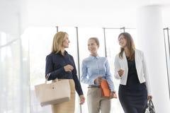 Mulheres de negócios de sorriso que falam ao andar contra a janela no escritório imagem de stock