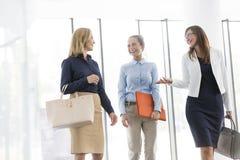 Mulheres de negócios de sorriso que falam ao andar no escritório imagens de stock
