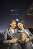 Mulheres de negócios novas que olham a tabuleta digital e o passeio Fotografia de Stock