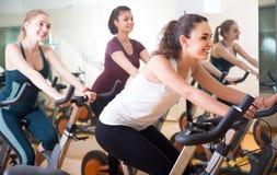 Mulheres de riso do treinamento diferente da idade em bicicletas de exercício Fotografia de Stock Royalty Free