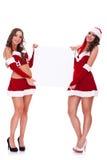 Mulheres de Santa que prendem uma placa em branco Fotos de Stock Royalty Free