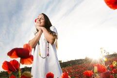 Mulheres de sorriso em um campo da papoila imagens de stock royalty free