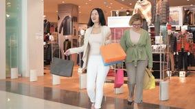 Mulheres de sorriso felizes que saem da loja da roupa com sacos As meninas dos amigos vão da entrada da loja luxuosa na alameda video estoque