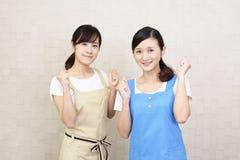 Mulheres de sorriso no avental fotografia de stock royalty free