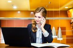 Mulheres de sorriso novas que sentam-se no café com um portátil e uma fala Fotos de Stock