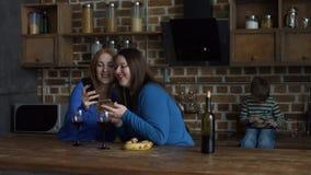 Mulheres de sorriso que bisbilhotam na cozinha doméstica video estoque