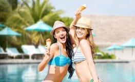 Mulheres de sorriso que comem o gelado sobre a piscina fotografia de stock