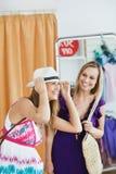 Mulheres de sorriso que escolhem a roupa junto foto de stock