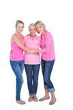 Mulheres de sorriso que vestem partes superiores e fitas cor-de-rosa para o câncer da mama Fotografia de Stock