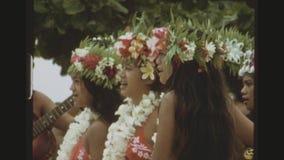 Mulheres de Tahitian em equipamentos tradicionais que cantam e que jogam a música filme