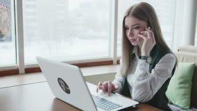 Mulheres de um negócio que trabalham com o portátil no café video estoque