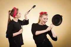 Mulheres denominadas retros que têm o divertimento com acessórios da cozinha fotografia de stock