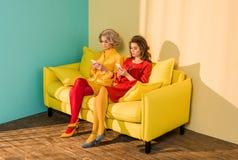 mulheres denominadas retros que usam smartphones ao descansar na boneca amarela do sofá fotografia de stock royalty free