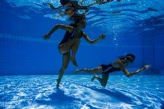 Mulheres desportivas novas que correm debaixo d'água Imagens de Stock Royalty Free
