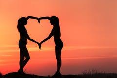 Mulheres desportivas novas que guardam as mãos na forma do coração no por do sol Imagens de Stock Royalty Free