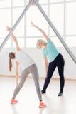 Mulheres desportivas positivas que fazem exercícios de dobra Fotografia de Stock