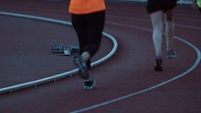 Mulheres desportivos que jugging na pista de decolagem no estádio exterior na noite filme
