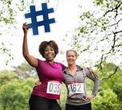 Mulheres diversas com ícone do hashtag no parque imagens de stock