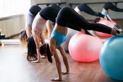 Mulheres do ajuste que fazem o exerc?cio em bolas ostentando no gym foto de stock royalty free
