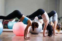 Mulheres do ajuste que fazem o exerc?cio em bolas ostentando no gym imagem de stock