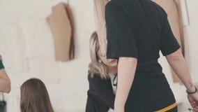 Mulheres do alfaiate que tomam medidas da camisa usando o medidor da fita video estoque