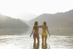 Mulheres do biquini com os braços em torno de estar no lago Fotografia de Stock