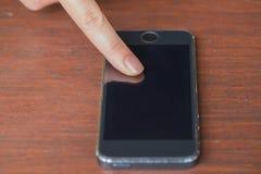 Mulheres do close up que usam o telefone da vista dianteira na tabela de madeira Fotos de Stock