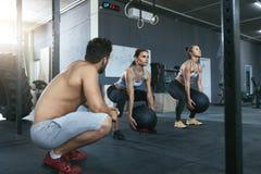 Mulheres do esporte que treinam com as bolas de Crossfit no Gym do exercício fotografia de stock royalty free