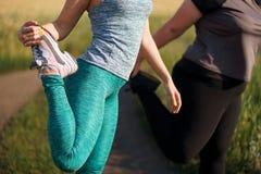 Mulheres do excesso de peso e do ajuste que aquecem-se antes de movimentar-se imagem de stock royalty free
