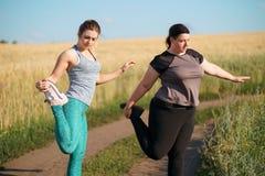 Mulheres do excesso de peso e do ajuste que aquecem-se antes de movimentar-se fotografia de stock royalty free