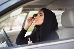 Mulheres do Oriente Médio que sentam-se dentro de um carro e que aplicam a composição Fotografia de Stock