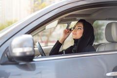 Mulheres do Oriente Médio que sentam-se dentro de um carro e que aplicam a composição Fotografia de Stock Royalty Free