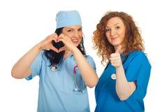 Mulheres dos doutores com forma e polegares do coração Fotos de Stock Royalty Free