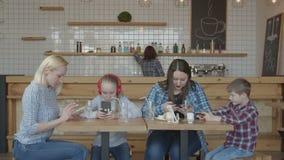 Mulheres e crianças que usam os telefones que sentam-se na tabela do café video estoque