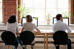 Mulheres e homem que sentam-se na opinião traseira traseira compartilhada do escritório fotos de stock royalty free