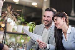 Mulheres e homens de negócio em uma ruptura em um café, em um riso e em um talkin fotografia de stock