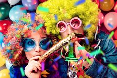 Mulheres e homens que comemoram no partido para a véspera ou o carnaval de anos novos fotos de stock royalty free