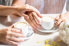 Mulheres e mãos dos homens com alianças de casamento, nos wi da tabela do café Fotos de Stock Royalty Free