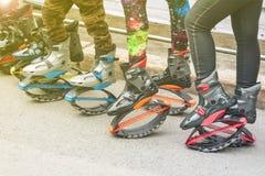 Mulheres e pés das crianças nas caneleiras e botas do salto com molas foto de stock royalty free