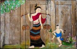 Mulheres e pintura tailandesas da criança na janela Imagem de Stock